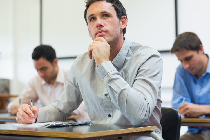 Mature students taking notes in classroom